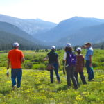 People standing in a field at CSU's Mountain Campus, looking toward the Mummy Range mountains.